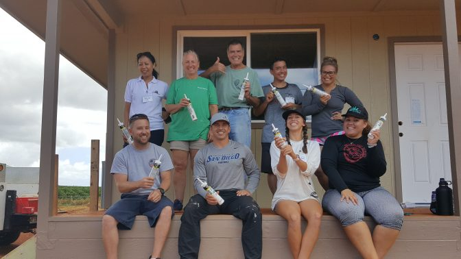 Eleele Habitat for Humanity. Group photo of workers sitting on porch holding contractor glue/adhesive bottles
