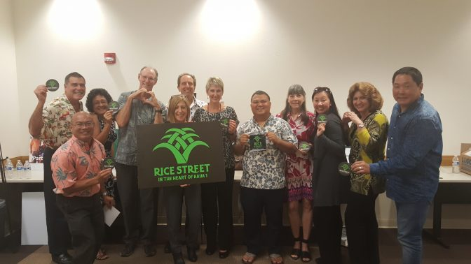 Group Photo with some of the KBR team holding a sign that reads 'Rice Street in the heart of Kauai'